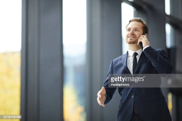 Cheerful optimistic handsome young bearded businessman in suit walking confidently over lobby and talking by cellphone