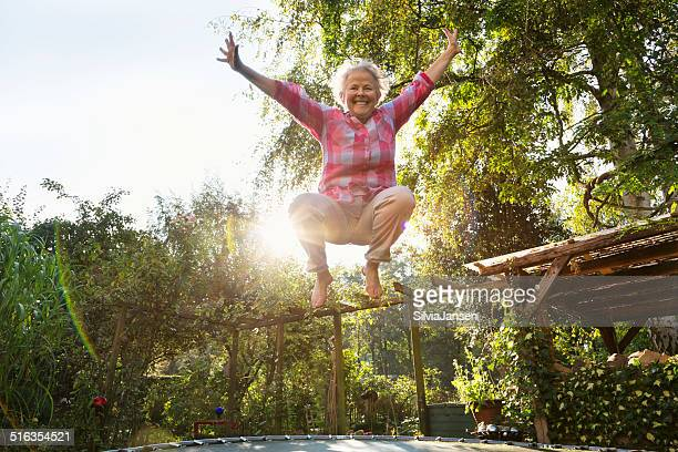 cheerful overweight senior woman jumping on trampoline