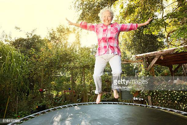 cheerful overweight senior woman jumping on trampoline - fat old lady stock photos and pictures