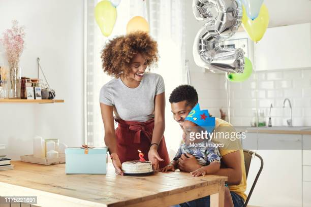cheerful parents celebrating birthday with son - number 2 stock pictures, royalty-free photos & images