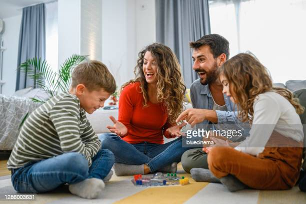 陽気な両親は、子供とボードゲームをプレイ。 - ボードゲーム ストックフォトと画像