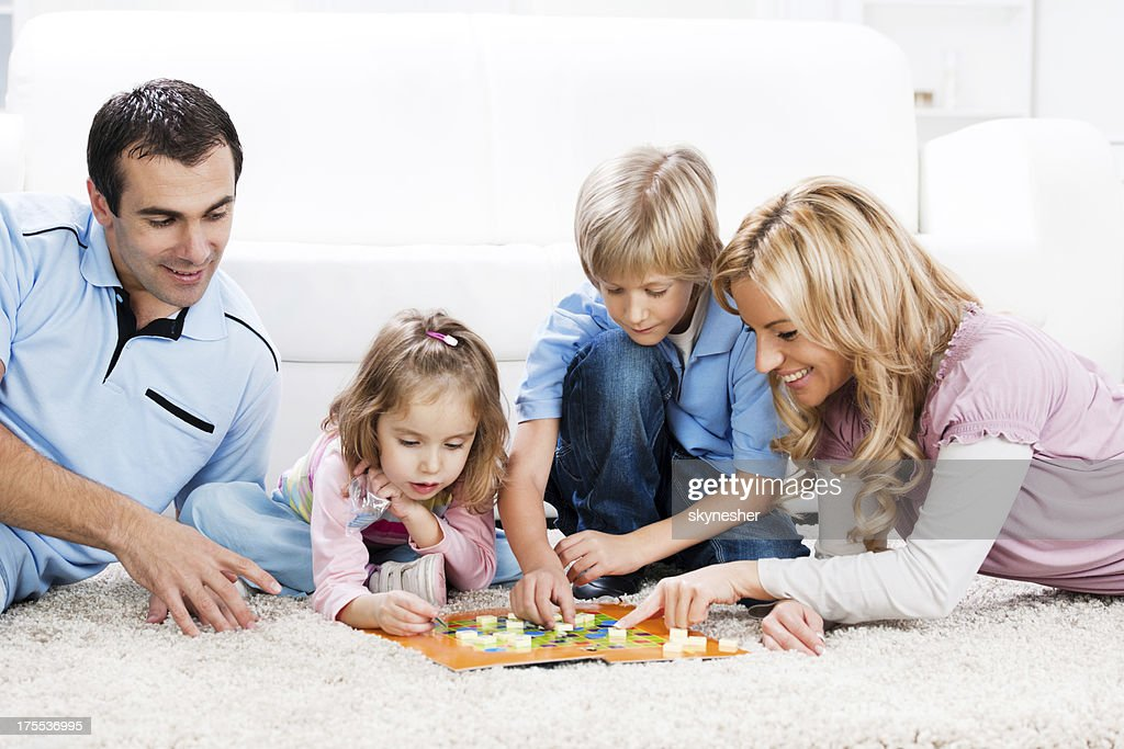 Cheerful parents playing board game with their children. : Stock Photo