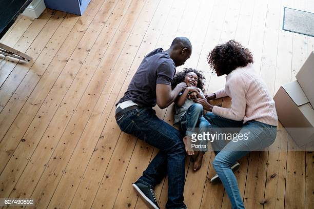 cheerful parents playing with son on at new home - african american family home stock photos and pictures