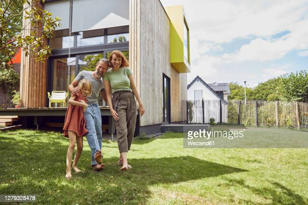 cheerful parents with daughter standing against tiny house in yard - haus stock-fotos und bilder