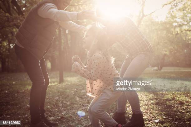 cheerful parents with one child playing in nature together. - family with one child stock pictures, royalty-free photos & images