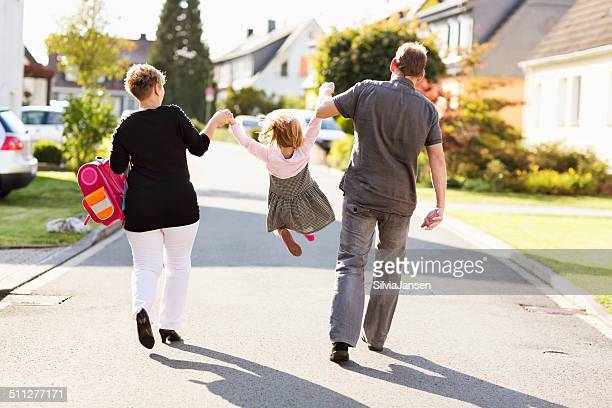 cheerful parents with schoolgirl swinging first day of school - first day of summer stock pictures, royalty-free photos & images