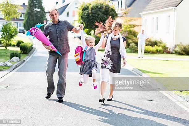 Fröhlich Eltern mit Schulkind-Nur Mädchen schwingen first day of school