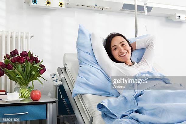 A cheerful patient lying in a hospital bed