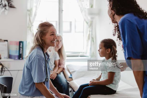 cheerful pediatrician talking to nurse while examining girl in medical clinic - healthcare stock pictures, royalty-free photos & images