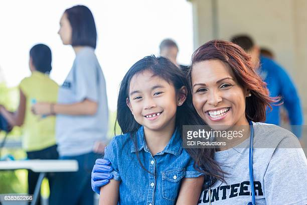 Cheerful pediatrician with young patient at outdoor health fair