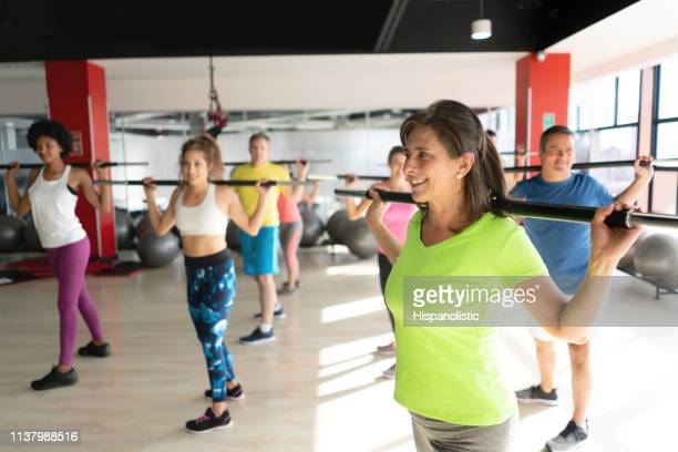 cheerful people at the gym in a weight lifting class working out smiling - hispanolistic stock photos and pictures