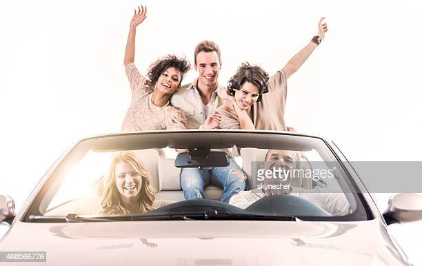 Cheerful people driving in a convertible car.