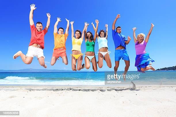 Entusiástico pessoas em t-shirts coloridas saltar na praia.