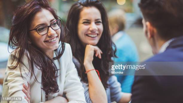 cheerful people sitting at the café - small group of people stock pictures, royalty-free photos & images