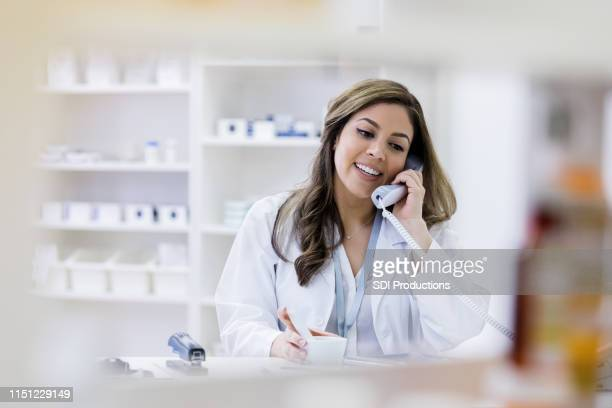 cheerful pharmacist consults with customer on telephone - pharmacist stock pictures, royalty-free photos & images