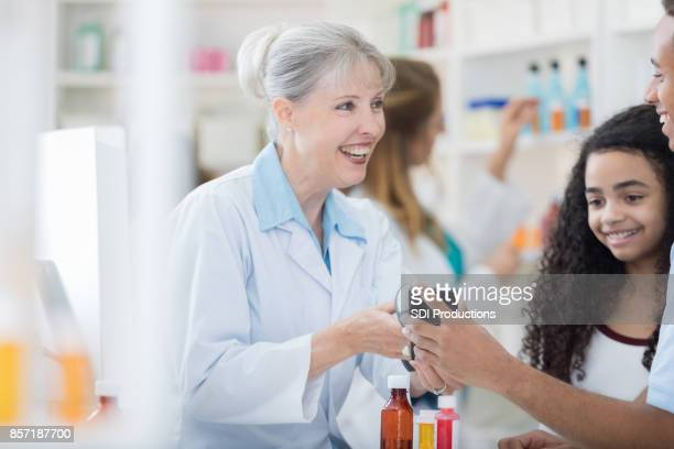 Cheerful pharmacist receives smart phone payment for prescription