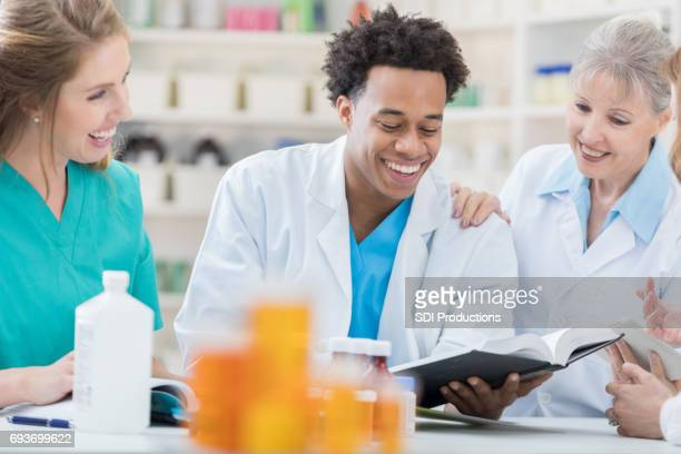 cheerful pharmacists review pharmacy textbook - instruction manual stock photos and pictures