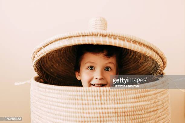 cheerful playful teen boy in wicker basket at home - school cane stock pictures, royalty-free photos & images