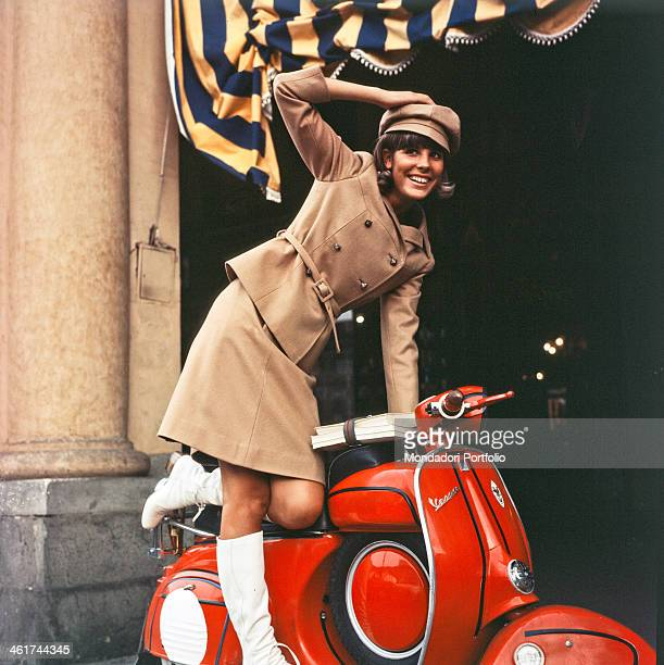 Cheerful portrait of Marisa Sannia who smiles while resting in balance on a red Piaggio Vespa the Sardinian singersongwriter wears a typical Sixties'...