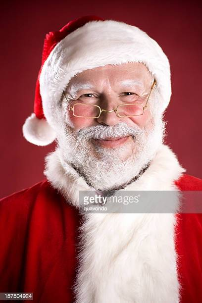cheerful portrait of santa claus smiling on red background, copyspace - santa face stockfoto's en -beelden