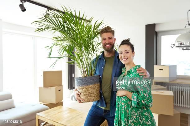 fröhliches schwangeres paar in ihrer neuen wohnung - izusek stock-fotos und bilder