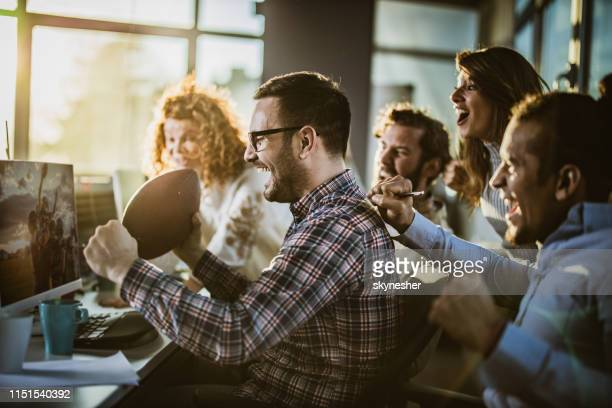 cheerful programmers cheering while watching their sports team on pc in the office. - match sport stock pictures, royalty-free photos & images