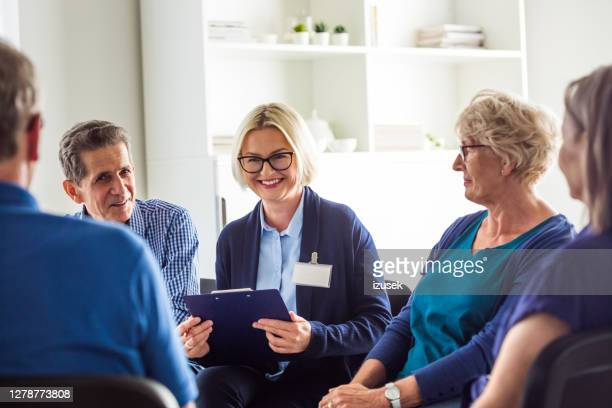 cheerful psychotherapist talking with senior people - meeting stock pictures, royalty-free photos & images