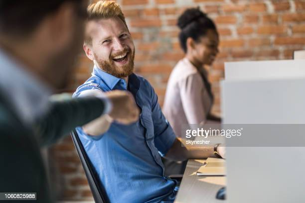 cheerful redhead businessman giving his colleague fist bump in the office. - fist bump stock pictures, royalty-free photos & images
