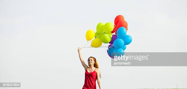 Cheerful redheaded woman holding brunch of balloons