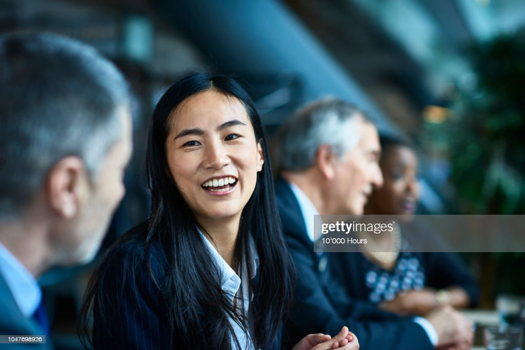 Cheerful relaxed businesswoman with manager in meeting : Stock Photo