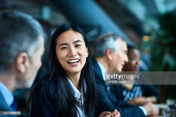 cheerful relaxed businesswoman with manager in meeting - asiatischer und indischer abstammung stock-fotos und bilder