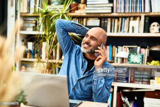 cheerful relaxed mature man on phone with laptop - businesswear stock pictures, royalty-free photos & images