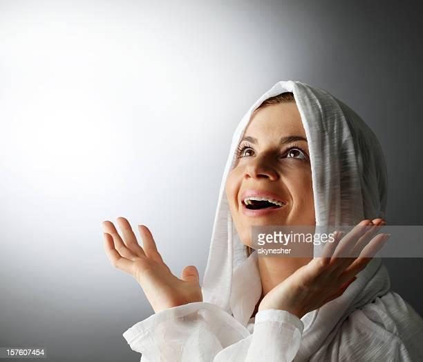 Fröhlich religiöse Frau mit offenen Händen.
