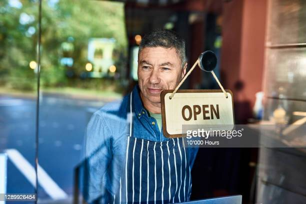 cheerful restaurant owner by open sign smiling - 40 44 years stock pictures, royalty-free photos & images