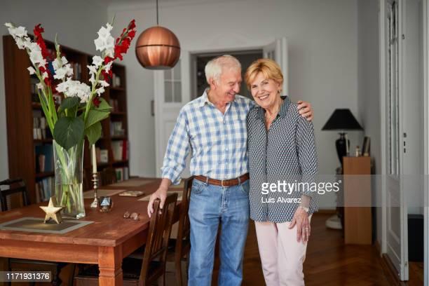 cheerful retired couple at home - pensionierung stock-fotos und bilder