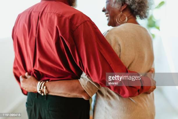 allegra coppia in pensione in piedi con le braccia intorno - dorso mano foto e immagini stock