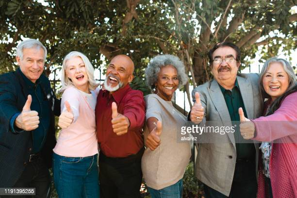 cheerful retired senior friends showing thumbs up - 60 69 years stock pictures, royalty-free photos & images