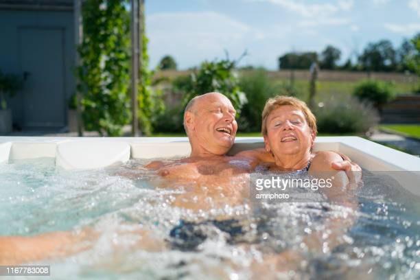 cheerful retiree couple enjoying summer day in whirlpool - hot tub stock pictures, royalty-free photos & images