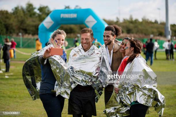 cheerful runners in foil blankets taking selfie - charity benefit stock pictures, royalty-free photos & images