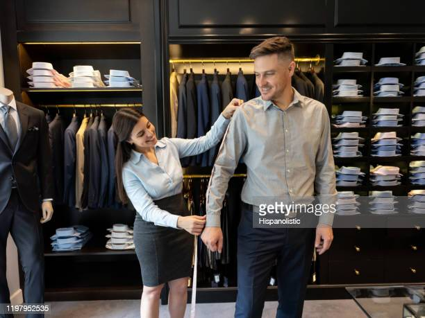 cheerful sales woman measuring the length of the arm of customer to tailor a button down shirt - length stock pictures, royalty-free photos & images