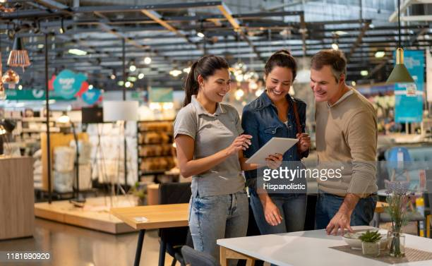cheerful sales woman showing a design on tablet to mid adult couple looking for furniture at a home store - furniture stock pictures, royalty-free photos & images