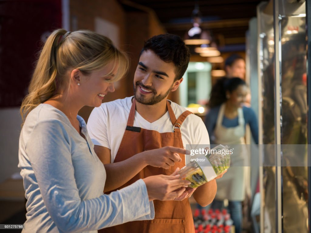 Cheerful salesman suggesting a new salad to a beautiful customer both smiling : Stock Photo