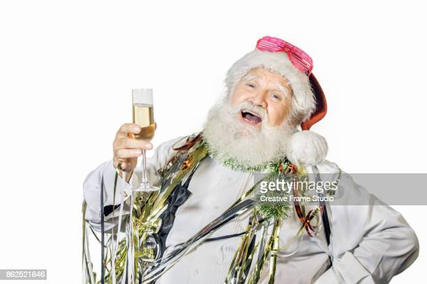 Cheerful Santa Claus celebrating and dancing  with a glass of champagne and party favors