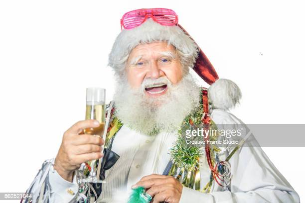 Cheerful Santa Claus celebrating  with a glass of champagne and party favors
