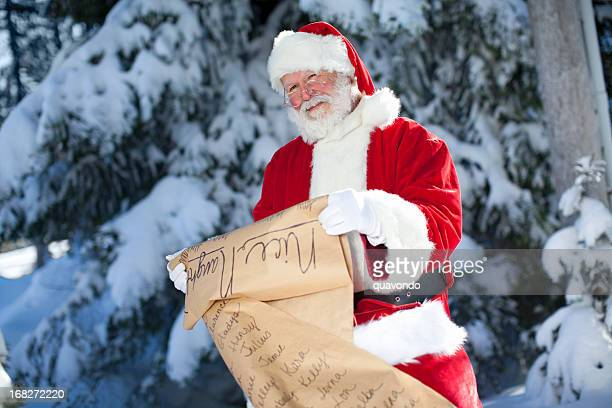 cheerful santa claus checking his list outdoors in winter snow - naughty santa stock photos and pictures