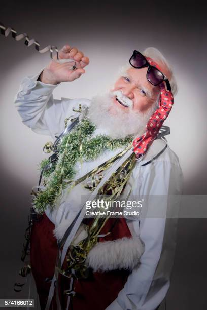 Cheerful Santa Claus on a party blowing streamers