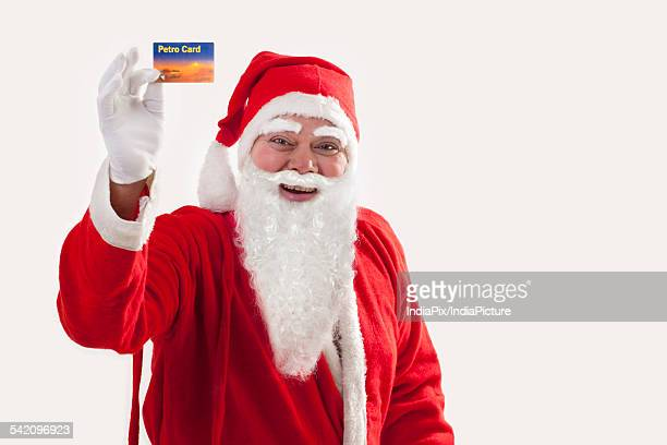 Cheerful Santa Claus showing petro card over colored background