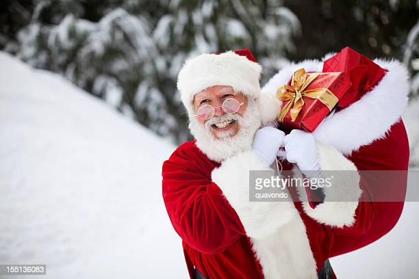 Cheerful Santa Claus Walking in Winter Snow with Christmas Gifts