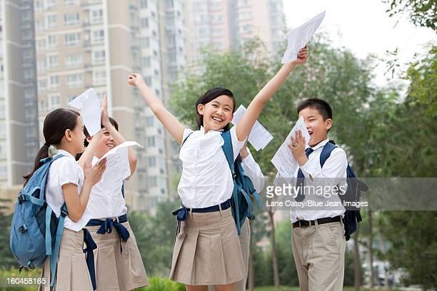 Cheerful schoolchildren in uniform celebrating for their test results