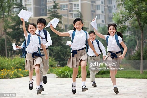 Cheerful schoolchildren in uniform with results lists in hands